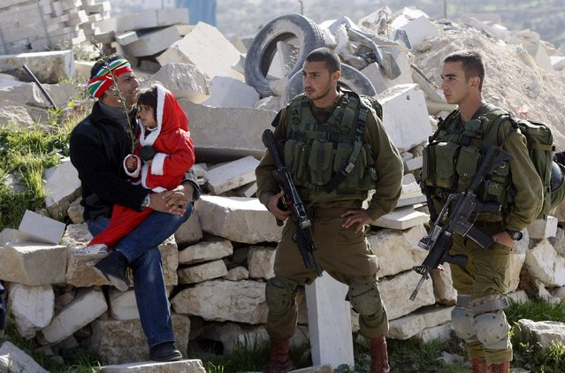A Palestinian protester holds his daughter, who is dressed as Santa Claus, as he sits next to Israeli soldiers during a weekly protest against Israeli settlements, in the village of Maasara near the West Bank city of Bethlehem January 2, 2015. (Photo by Mussa Qawasma/Reuters)