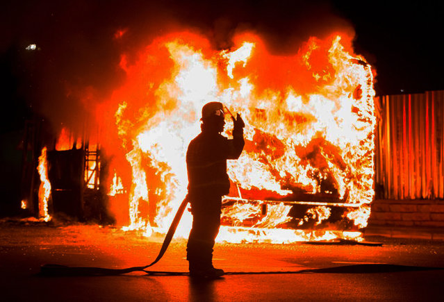 A fireman stands at a burning bus in Braamfontein, Johannesburg, South Africa, Tuesday, October 25, 2016. (Photo by Yeshiel Panchia/AP Photo)