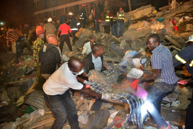 Rescue workers help the injured at the site of a multi-storey building collapse  in the capital Nairobi, Kenya Sunday, January 4, 2015. (Photo by AP Photo)
