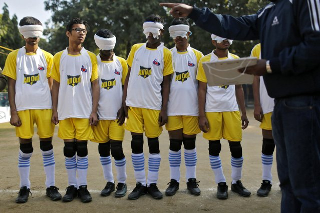 Visually impaired students of a school for the blind listen to their instructor before the start of a soccer match inside their school in New Delhi January 5, 2015. (Photo by Anindito Mukherjee/Reuters)