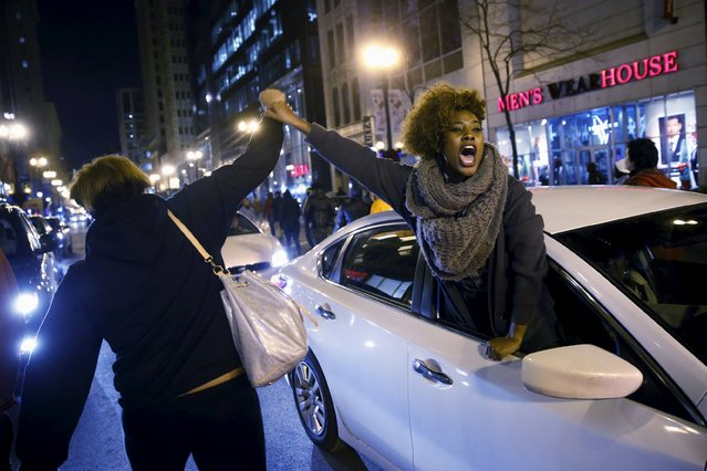 A woman greets protesters out of a car window during a protest after the release of a video showing the shooting of Laquan McDonald, in Chicago, Illinois, November 25, 2015. McDonald, 17, was fatally shot by a Chicago police officer in October 2014. (Photo by Andrew Nelles/Reuters)