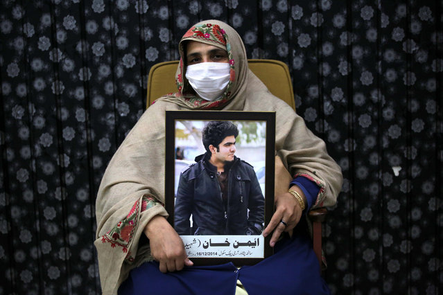 A mother holds the portrait of victim of Army Public School (APS) attack, during a ceremony on the eve of the sixth anniversary of the Peshawar school attack, in Peshawar, Pakistan, 15 December 2020. In December 2014 Taliban militants attacked the army-run Army Public School in the north-western city of Peshawar, where about 150 people, mostly students, were killed. (Photo by Bilawal Arbab/EPA/EFE)