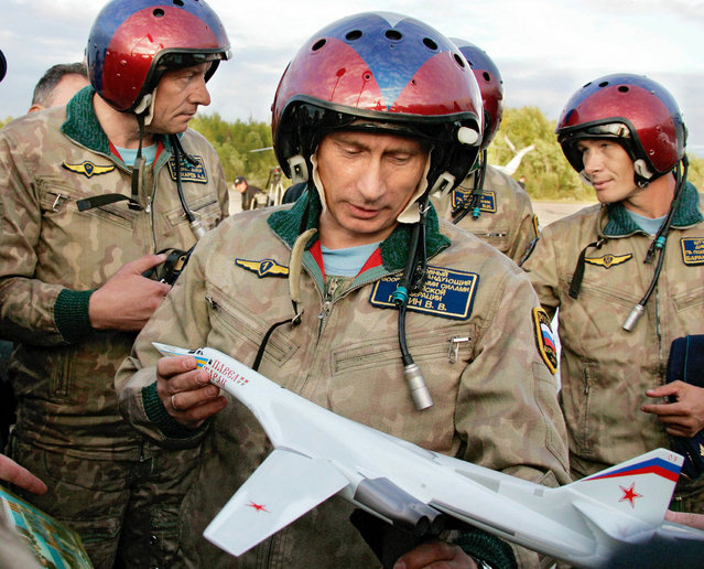 Vladimir Putin looks at a model of the Tupolev TU-160 bomber, or Blackjack, that was presented to him on his arrival in Olenegorsk, Russia, August 16, 2005. Putin flew in the Tupolev TU-160 bomber and took part in the launch of cruise missiles in the Arctic north. (Photo by Reuters/ITAR-TASS/Presidential Press Service)