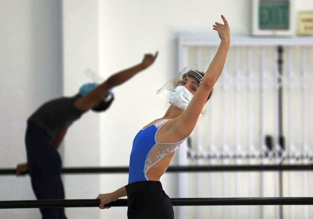 Cape Town City Ballet company dancer Olivia Parfitt, wearing a face mask and shield as she does exercises when the company returned for their first day back at work after more than two months in lockdown in Cape Town, South Africa, Friday, June 5, 2020. The dancers have been training at home due to strict lockdown regulations that have been implemented in a bid to prevent the spread of coronavirus. (Photo by Nardus Engelbrecht/AP Photo)