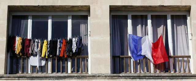 A French national flag hangs from a balcony in Marseille, France, November 27, 2015 as the French President called on all French citizens to hang the tricolour national flag from their windows on Friday to pay tribute to the victims of the Paris attacks during a national day of homage. (Photo by Jean-Paul Pelissier/Reuters)