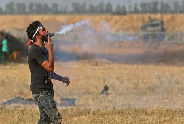 A Palestinian protester holds a tear gas canister in his mouth during a demonstration along the border with Israel east of Khan Yunis in the southern Gaza strip on June 1, 2018. (Photo by Said Khatib/AFP Photo)