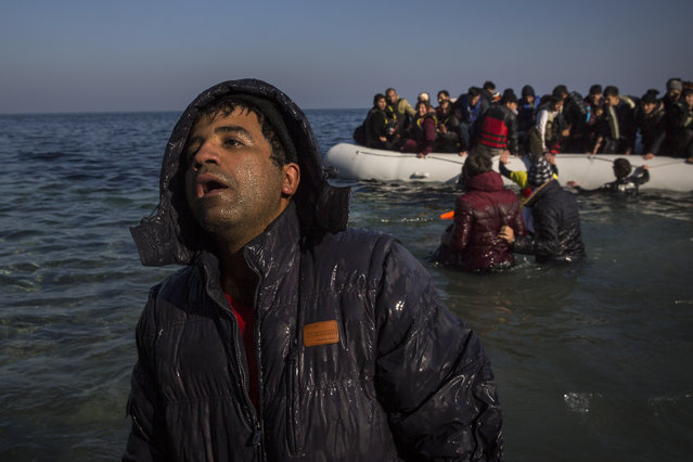 An exhausted man disembarks from a dinghy on a beach next to the town of Mytilene, after crossing a part of the Aegean sea from the Turkey's coast to the northeastern Greek island of Lesbos, on Sunday, December 6, 2015. Greece is the main point of entry into the EU for people fleeing war and poverty at home, with the vast majority of the 700,000 people who have entered the country this year reaching Greek islands from the nearby Turkish coast. (Photo by Santi Palacios/AP Photo)