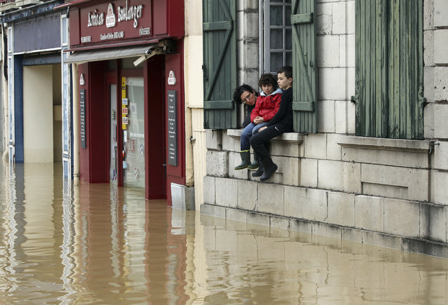 A mother and her children watch from their house the level of flooded water caused by heavy rain and thunder storms, in Salies-de-Bearn, southwestern France, Wednesday, June 13, 2018. (Photo by Bob Edme/AP Photo)