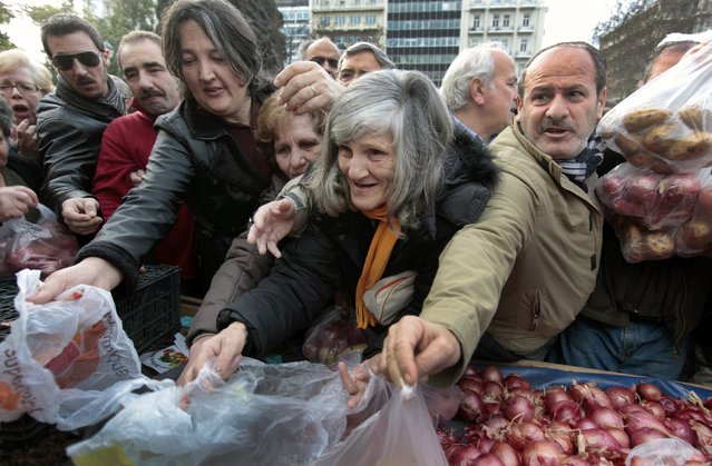 Greeks struggle as they wait to receive free onions and other vegetables offered by farmers in Syntagma Square in this January 25, 2012 file photo. (Photo by Yannis Behrakis/Reuters)