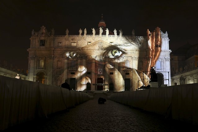 """A picture from US. photographer Steve McCurry, part of an art projection featuring images of humanity and climate change artistically rendered by Obscura Digital, is projected onto the facade of St. Peter's Basilica, as part of an installation entitled """"Fiat Lux: Illuminating our Common Home"""" as a gift to Pope Francis on the opening day of the Extraordinary Jubilee, at the Vatican, December 8, 2015. (Photo by Stefano Rellandini/Reuters)"""