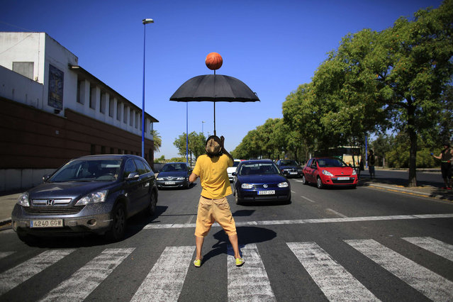 """Uilli, a juggler from the """"Circo Tropico"""" company, performs at a zebra crossing in the Andalusian capital of Seville, southern Spain, June 24, 2013. (Photo by Marcelo del Pozo/Reuters)"""