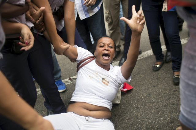 """Cuban security personnel detain a member of the Ladies in White dissident group during a protest on International Human Rights Day, Havana December 10, 2015. Cuban police detained at least six protesters shouting """"Freedom"""" and """"Long live human rights"""" in Havana on Thursday and dissidents reported 100 arrests nationwide on U.N. Human Rights Day, when some Cubans seek to hold unauthorized demonstrations. (Photo by Alexandre Meneghini/Reuters)"""