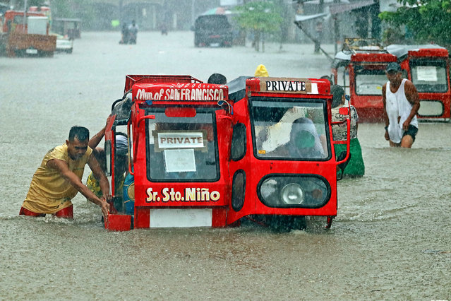 People push a half-submerged tricycle through a flooded street due to heavy rains caused by tropical depression Vicky in San Francisco town, Agusan del sur province on the southern island of Mindanao on December 18, 2020. (Photo by Erwin Mascarinas/AFP Photo)