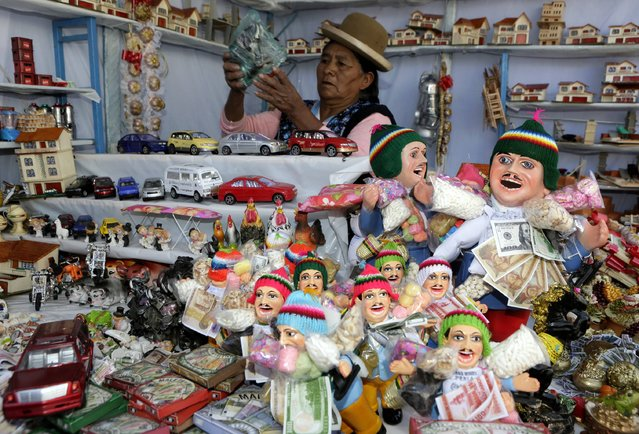 "A woman sells statues of the Ekeko, god of fortune, at the traditional ""Alasitas"" fair in La Paz January 24, 2015. During the fair, Bolivians buy miniature versions of goods like cars, money and houses they would like to own in real life during the year. (Photo by David Mercado/Reuters)"