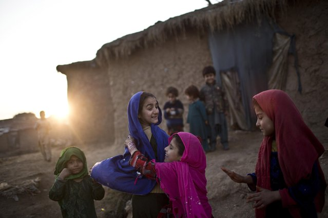 Afghan refugee girls play in a slum on the outskirts of Islamabad, Pakistan, Saturday, January 17, 2015. (Photo by Muhammed Muheisen/AP Photo)