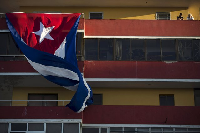 People watch a concert by Puerto Rican singer Olga Tanon from the balcony of a building as a Cuban national flag flutters in Havana December 12, 2015. (Photo by Alexandre Meneghini/Reuters)