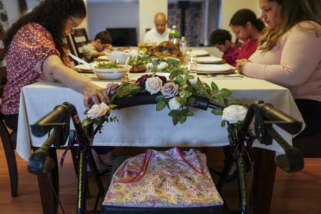 Vivian Zayas holds onto the walker once belonging to her recently deceased mother Ana Martinez while her family prays before Thanksgiving dinner, Thursday, November 26, 2020, in Deer Park, N.Y. Ana Martinez died at 78 on April 1 while recovering at a nursing home from a knee replacement. The family is having their traditional meal of turkey, yams, green beans and rice and beans — but Zayas is removing a seat from the table at her home in Deer Park, New York, and putting her mother's walker in its place. (Photo by John Minchillo/AP Photo)