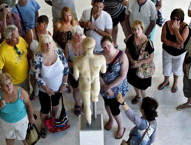 Tourists admire an ancient statue in the hall of the archaic period at the Athens Acropolis Museum, on July 19, 2013. (Photo by John Kolesidis /Reuters)
