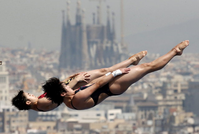 China's Chen Roulin, right, and Liu Huixia perform during a synchronized 10-meter platform diving training session ahead of the FINA Swimming World Championships in Barcelona, Spain, Friday, July 19, 2013. In the background is the Sagrada Familia church. (Photo by Michael Sohn/AP Photo)