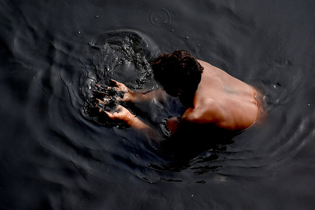 A man looks for valuables in the polluted Yamuna River in New Delhi on March 9, 2021. (Photo by Money Sharma/AFP Photo)