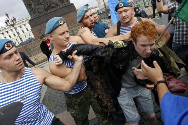Former Russian paratroopers shove gay rights activist Kirill Kalugin aside to stop his one-man protest in St. Petersburg, August 2, 2013. The former servicemen were gathered in central St. Petersburg to celebrate Russian Paratroopers Day, an annual holiday for the Russian airborne troops celebrated since the Soviet era days. (Photo by Alexander Demianchuk/Reuters)