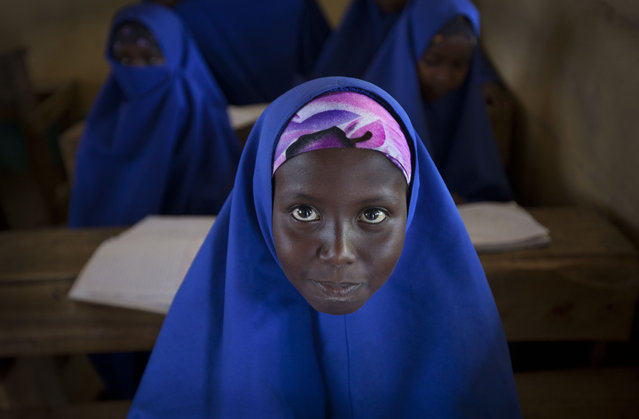 A Somali schoolgirl sits at her desk during a lesson in the town of Dhobley, currently under control by Kenyan military and Somali government forces, in Somalia Tuesday, February 21, 2012. (Photo by Ben Curtis/AP Photo)