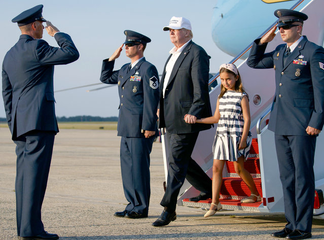 President Donald Trump, holding the hand of his granddaughter Arabella Kushner, arrives on Air Force One, Sunday, July 29, 2018, in Andrews Air Force Base, Md., en route to Washington as they return from Trump National Golf Club in Bedminster, N.J.. (Photo by Carolyn Kaster/AP Photo)