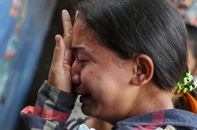 Thae Nu Naing, sister of Saw Pyae Naing weeps by his body at their home in Mandalay, Myanmar, Sunday, March 14, 2021. Saw Pyae Naing, a 21-year old anti-coup protester was shot and killed by Myanmar security forces during a demonstration on Saturday, according to his family. (Photo by AP Photo/Stringer)