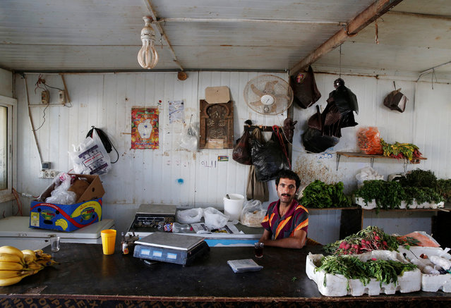 A Syrian refugee man sits inside his shop in Zaatari refugee camp near the border with Syria, in Mafraq, Jordan October 15, 2016. (Photo by Ammar Awad/Reuters)