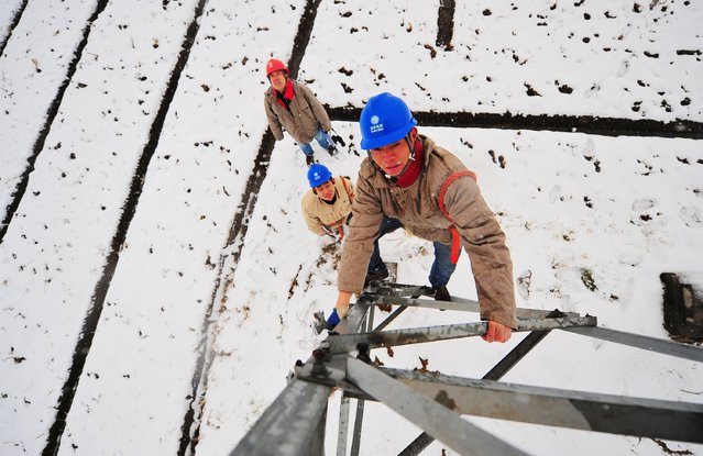 Employees check on a pylon as it snows in Hefei, Anhui province, January 28, 2015. China plans to cut its growth target to around 7 percent in 2015, its lowest goal in 11 years, sources said, as policymakers try to manage slowing growth, job creation and pursuing reforms intended to make the economy more driven by market forces. (Photo by Reuters/Stringer)