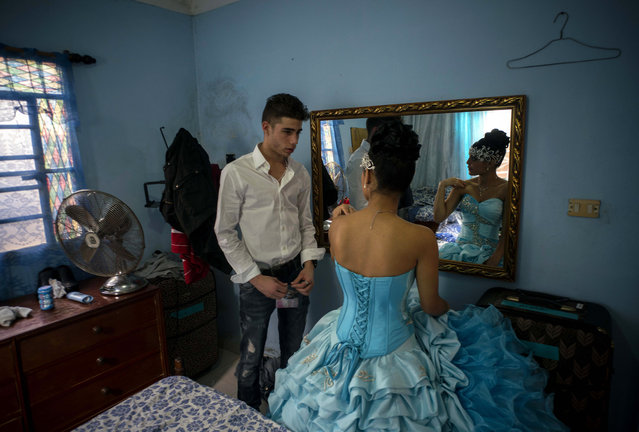 In this December 20, 2015 photo, Daniela Santos Torres, 15, speaks with her boyfriend Erick before her quinceanera party in the town of Punta Brava near Havana, Cuba. (Photo by Ramon Espinosa/AP Photo)