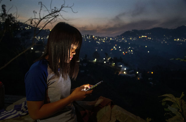 A police officer who fled Myanmar following a military coup looks at her phone at an undisclosed location bordering Myanmar, in the northeastern Indian state of Mizoram, Thursday, March 18, 2021. Villagers in Mizoram have given shelter to 34 Myanmar police personnel and 1 fire fighter, who crossed over to the state over the last two weeks. Those who escaped spend their time watching local television and doing daily chores. Some of them have carried mobile phones and are trying to connect to families they were forced to leave behind. At night, all of them go to sleep on mattresses laid on the floor of a single room. (Photo by Anupam Nath/AP Photo)