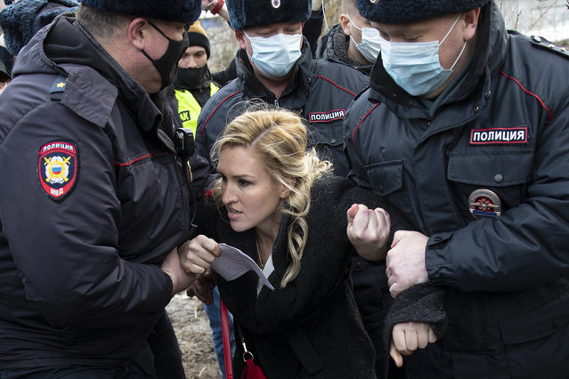 Police officers detain the Alliance of Doctors union's leader Anastasia Vasilyeva at the prison colony IK-2, which stands out among Russian penitentiary facilities for its particularly strict regime, in Pokrov in the Vladimir region, 85 kilometers (53 miles) east of Moscow, Russia, Tuesday, April 6, 2021. Doctors from the Navalny-backed Alliance of Doctors announced going to the Pokrov prison on Tuesday to demand the opposition leader gets qualified medical help from independent doctors after he complained about pain in his leg and back. (Photo by Pavel Golovkin/AP Photo)