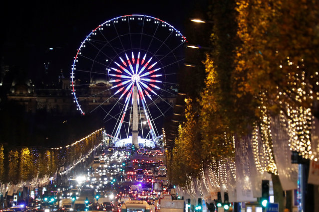 Christmas holiday lights hang from trees to illuminate Champs Elysees avenue in Paris as rush hour traffic fills the avenue leading down to the Giant Ferris Wheel at place de la Concorde in Paris, France, November 21, 2016. (Photo by Charles Platiau/Reuters)
