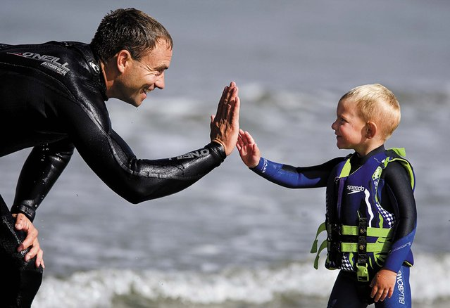 Triston gets a high five from his father after riding all the way to the sand. (Photo by Joe Johnston/The Tribune of San Luis Obispo)