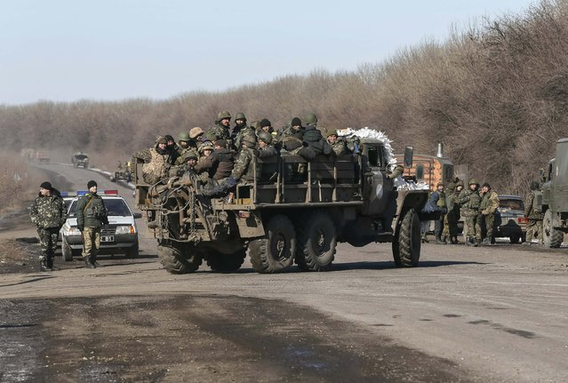 Ukrainian servicemen ride on a military vehicle as they leave an area around Debaltseve, eastern Ukraine near Artemivsk February 18, 2015. (Photo by Gleb Garanich/Reuters)