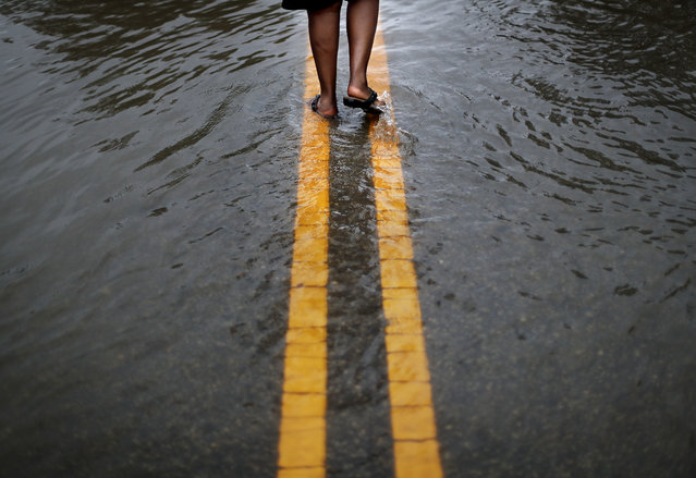 """Helen McKoy walks down a flooded street in her neighborhood as Florence continues to dump heavy rain in Fayetteville, N.C., Sunday, September 16, 2018. """"I've never seen it like this before"""", said McCoy of the rising water down the street from her home. """"Whatever God got for me he's going to give it to me. He said he's going to take care of us and that's what I'm going to have to live on"""". (Photo by David Goldman/AP Photo)"""
