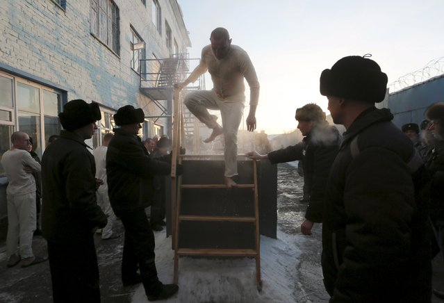 An inmate walks out after immersing himself in water at high-security penal colony number 6 on the eve of the Orthodox Epiphany, with the air temperature at about minus 29 degrees Celsius (minus 20.2 degrees Fahrenheit), in the Siberian city of Omsk, Russia, January 18, 2016. (Photo by Dmitry Feoktistov/Reuters)