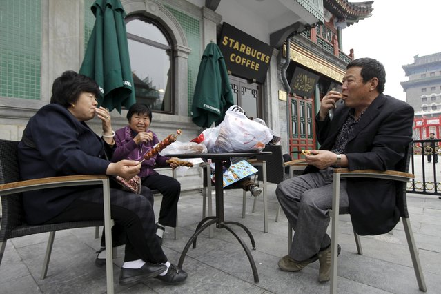 People eat snacks in a yard of a Starbucks coffee store at Qianmen Commercial Street in central Beijing, in this April 19, 2012 file photo. Starbucks Corp, the world's largest coffee chain, said on Tuesday it aims to open 500 stores in China in 2016, shrugging off a slowdown in the world's second-largest economy that has hit global retailers. (Photo by Jason Lee/Reuters)