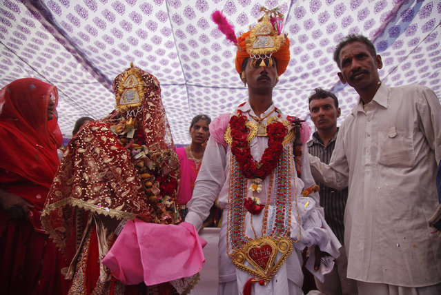 An Indian bride and groom in traditional attire perform wedding rituals during a mass marriage of thirty five couple belonging to Rajasthan's Sargara community in Ahmadabad, Gujarat state, India, Sunday, January 24, 2016.Mass marriages in India are organized by social organizations primarily to help the economically backward families who cannot afford the high ceremony costs as well as the customary dowry and expensive gifts that are still prevalent in many communities. (Photo by Ajit Solanki/AP Photo)