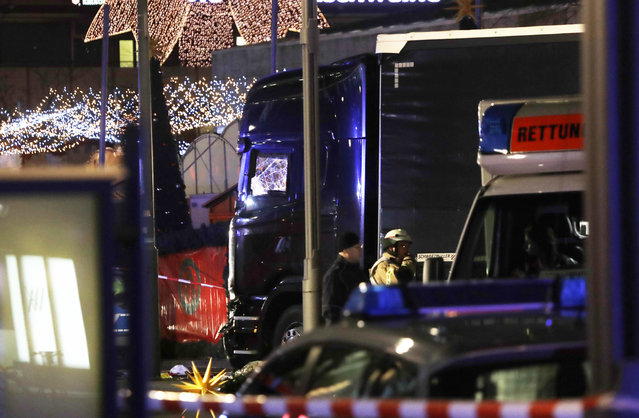 Police stand beside a damaged truck which ran into crowded Christmas market in Berliin Berlin, Germany, Monday, December 19, 2016. (Photo by Michael Sohn/AP Photo)