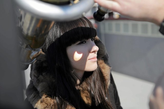 The shadow of a partial eclipse is cast on to the cheek of a student on the roof of the Jana Dlugosza Academy in Czestochowa, Poland March 20, 2015. (Photo by Grzegorz Skowronek/Reuters/Agencja Gazeta)