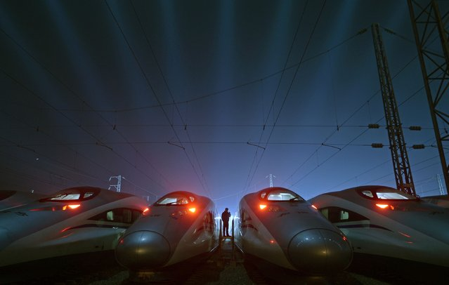 A worker stands among CRH (China Railway High-speed) Harmony bullet trains at a high-speed train maintenance base in Wuhan, Hubei province March 9, 2015. China is poised to embark on a fresh round of industrial consolidation, as part of a sweeping plan to reinvigorate the country's inefficient state-owned enterprises and raise the global competitiveness of domestic industry. (Photo by Reuters/Stringer)