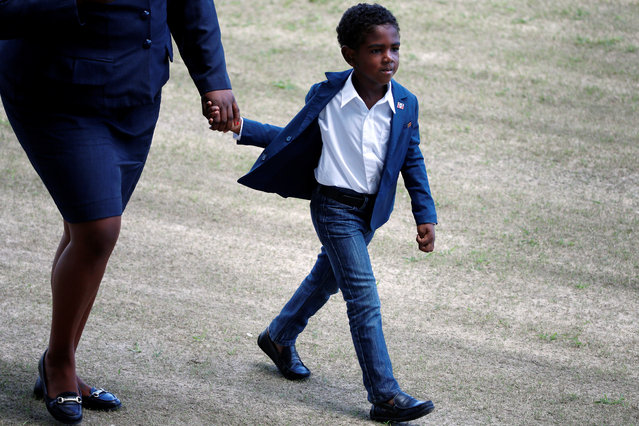 ANTIGUA: A child holds hands as he walks out of a sporting event with youth that Prince Harry attended during his official visit in St. Johns, Antigua November 21, 2016. (Photo by Carlo Allegri/Reuters)