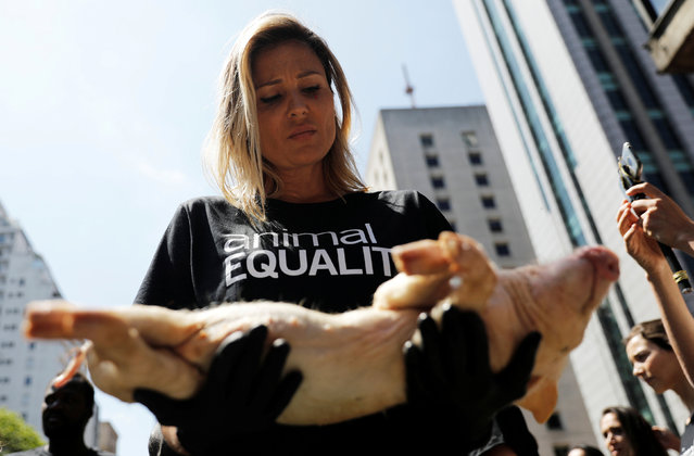 An animal rights activist from Animal Equality holds a dead pig during a gathering to protest the treatment of animals at Paulista avenue in Sao Paulo, Brazil, December 9, 2018. (Photo by Nacho Doce/Reuters)