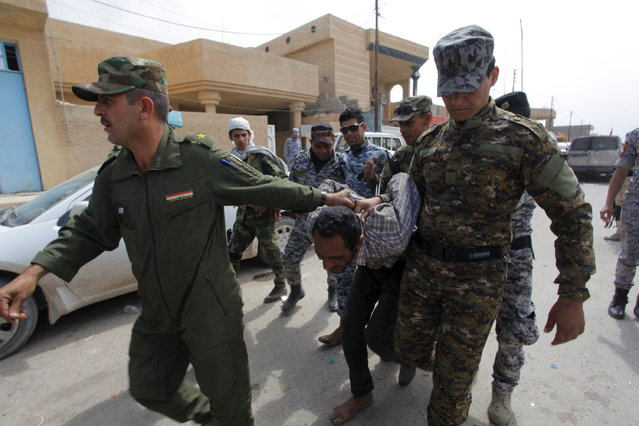 Iraqi security forces arrest a member of the Islamic State in Tikrit April 1, 2015. (Photo by Alaa Al-Marjani/Reuters)