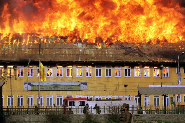 An Indian soldier walks in front of a government building on fire after an attack in Srinagar, April 2005. (Photo by Desmond Boylan/Reuters)