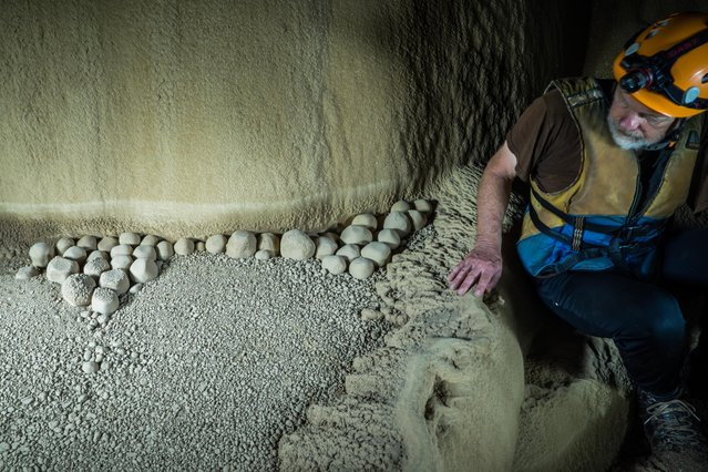 "American cave explorer Dave Pierce marvels at giant cave pearls, some with a hexagonal shape, in the ""Oxbow"" section of the cave. These may well be the largest known examples on earth. Cave pearls grow like pearls in an oyster with concentric layers of calcite slowly building up year after year on March 2015 at Tham Khoun Ex, Laos. (Photo by John Spies/Barcroft Media/ABACAPress)"