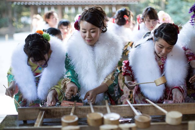 In this photo taken on January 6, 2017, twenty-year-old Japanese female tour guides, dressed in traditional kimonos, wash their hands during a purification ceremony to celebrate their Coming-of-Age at Meiji shrine in Tokyo. (Photo by Behrouz Mehri/AFP Photo)