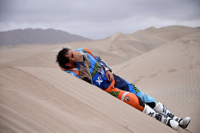 In this January 9, 2019 photo, Marcos Colvero of Brazil lies on the dunes after he crashed on his KTM motorbike during the third stage of the Dakar Rally between San Juan de Marcona and Arequipa, Peru. (Photo by Franck Fife/Pool Photo via AP Photo)